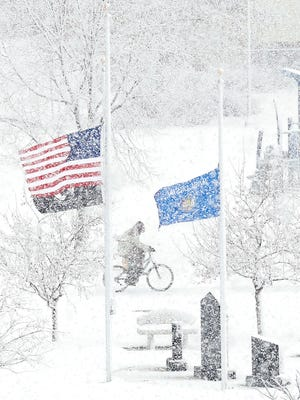With flags at half-staff, a bicyclist rides through Hamilton Park Wednesday.