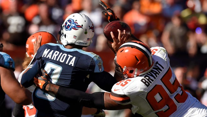 Titans quarterback Marcus Mariota (8) has the ball knocked away by Cleveland Browns defensive end Armonty Bryant (95).