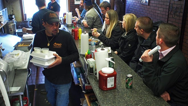 Matt Mothershead, owner of Mama's Phried & Phillys, grabs a customer's order Tuesday, Dec. 6, 2016, at the restaurant in downtown Sioux Falls. Both Mama's Phried & Phillys and Oshima Sushi Japanese Cuisine on 10th Street between Phillips and Mall Avenues across from the site of the Copper Lounge building collapse opened Tuesday after having been closed since the collapse.
