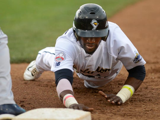 York's Justin Greene slides safely back to first base during a 2014 game. He stole 31 bases in his only season with the Revolution.