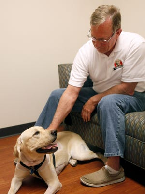 Scott Clare of Bakersfield, Calif., pets his labrador, Buck-O, during an appointment at MedVet on June 23.