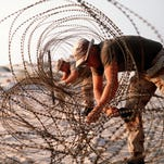 U.S. Marines place concertina wire around their encampment during Operation Desert Shield.