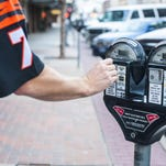 Olin McCrumb puts coins in a parking meter on Central Avenue Thursday, Nov. 5, 2015.