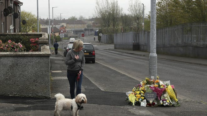 A woman reacts as she stops to pay her respects at the scene Saturday April 20, 2019, in Londonderry, Northern Ireland, where 29-year old journalist Lyra McKee was fatally shot.