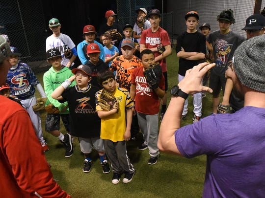 Sam Wilson, right, and Austin House coach a group of kids during the Grinders for Grace camp Jan. 9, 2016, at the Strike Zone training facility in Farmington.