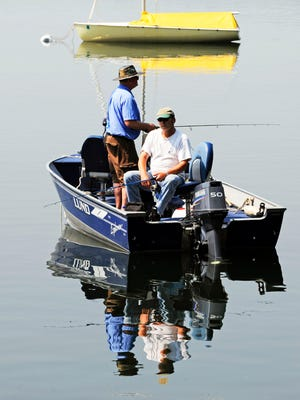 In this June 24, 2010 file photo, two fishermen enjoy the still waters to fish on Lake Calhoun in Minneapolis. The state's Game and Fish Fund, which finances crucial work at the Department of Natural Resources, is headed into the red. The money comes from license fees that aren't keeping up with spending on fish and wildlife programs. (AP Photo/Jim Mone, File)