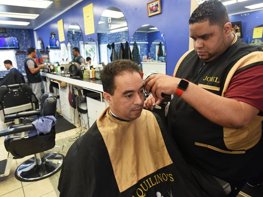 Owner Alberto Marte trims the hair of his worker Juan