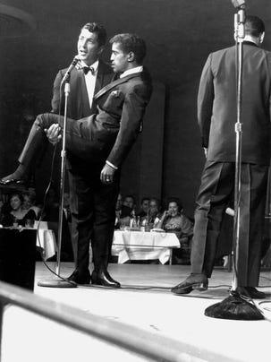 Dean Martin carries Sammy Davis Jr. during their nightly