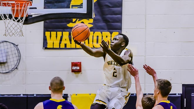 Emmanuel Gildo ,top, of Waverly takes the ball to the DeWitt basket during their game Friday January 8, 2016 in Delta Township. KEVIN W. FOWLER PHOTO