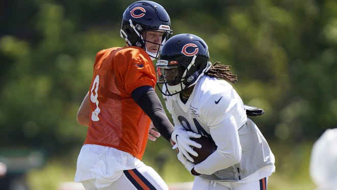 Chicago Bears backup quarterback Nick Foles, left, hands the ball off to wide receiver Cordarrelle Patterson during a camp practice in Lake Forest on Saturday, Aug. 22.