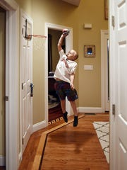 Max Omphalius, 8, plays hoop in the hallway of the family's Beekman home. Nov. 20, 2014
