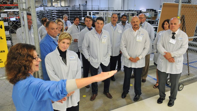 Susan Badgio of MACK leads a group of Brevard lawmakers, business leaders, and others wearing smocks, on a 2016 tour of MACK Technologies in West Melbourne. MACK sponsored the event for Manufacturers Association Florida's Space Coast (MASC), an initiative of the Economic Development Commission (EDC).