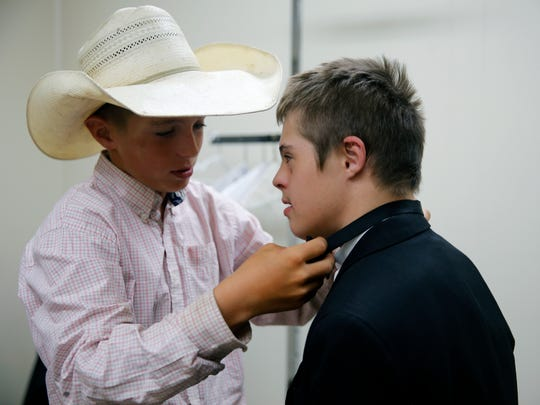 Cash Carruth, 11, helps his brother, Joshua Carruth, 13, put on a bow tie, Friday as Joshua Carruth tried on clothes for an upcoming Special Olympics prom in Farmington.