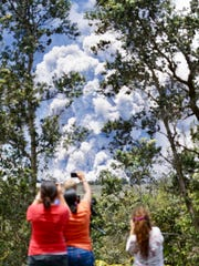 Onlookers take photos of the Kilauea volcanic eruption
