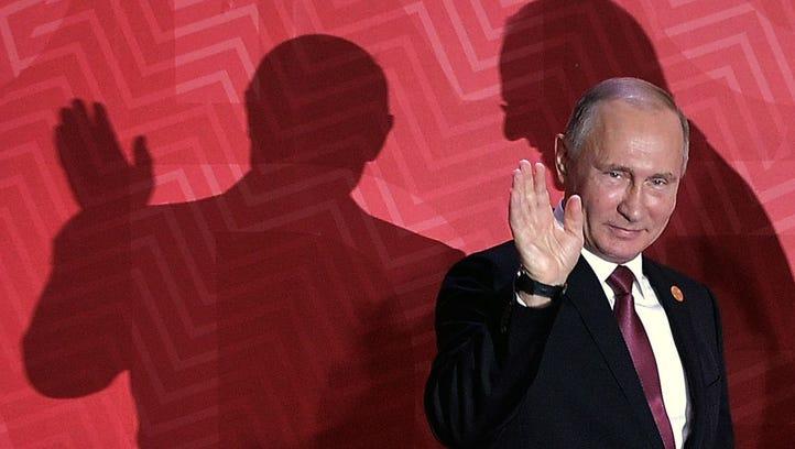 Russia's President Vladimir Putin waves as he arrives