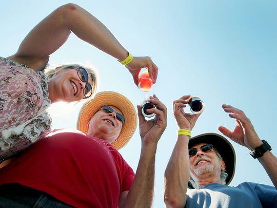 Elvina Baxter of Bremerton, left, joins John Seiler, center, of Spanaway, and Kyle Bowman of Federal Way on a beer toast Saturday on the Bremerton Boardwalk. They were out on a sunny afternoon at the Bremerton Summer BrewFest.