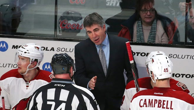 Feb 1, 2015: Linesman Lonnie Cameron (74) talks with Arizona Coyotes head coach Dave Tippett (C) against Montreal Canadiens during the second period at Bell Centre.