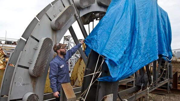 Jordan Adams, an employee of Caldwell Marine International, shows a power quadrant used to transfer cable from a ship to the company's barge at its Bass River marine yard.