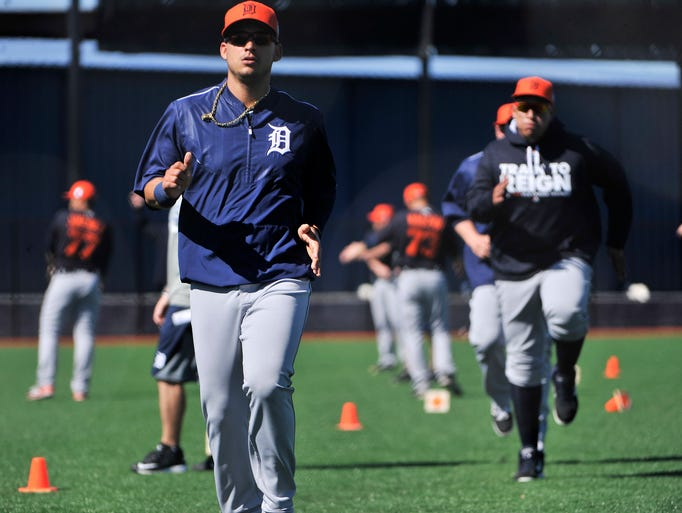 Tigers shortstop Jose Iglesias warms up, left, with