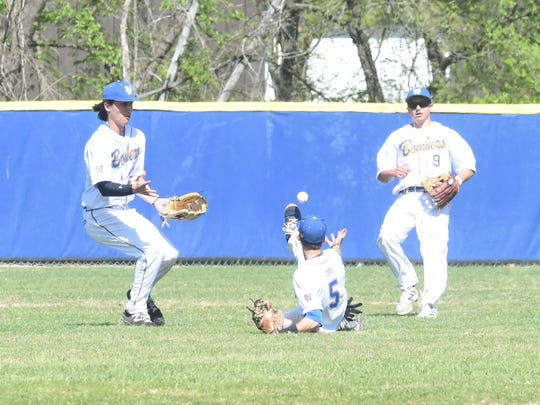 Mountain Home's Luke Kruse, Josh Prinner and Asa Smith converge on a fly ball during a game earlier this season.