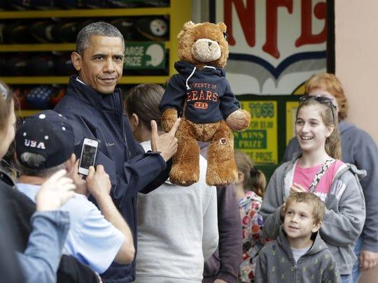 President Obama holds up a stuffed bear that N.J. Gov.