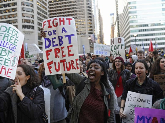 People march to Philadelphia City Hall over the heavy burden of student loans, as expressed on these signs. (Clem Murray/Philadelphia Inquirer/TNS)
