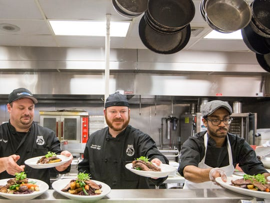 "From left: Chefs Michael Stiglitz and Christopher Meyer and cook Reuben Dhanawade place plated dishes up for servers at the ""pop-up"" beer dinner."