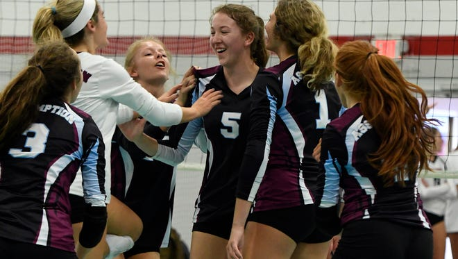 Assumption's Rylee Rader, center, is congratulated by teammates following a score during the championship match of the Louisville Invitational Volleyball Tournament at the Ohio Valley Volleyball Center, Saturday, Sep. 9, 2017 in Louisville.
