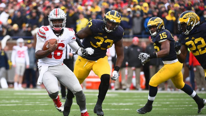 Ohio State Buckeyes quarterback J.T. Barrett (16) runs the ball against Michigan Wolverines defensive end Taco Charlton (33) during the game against the Michigan Wolverines at Michigan Stadium.