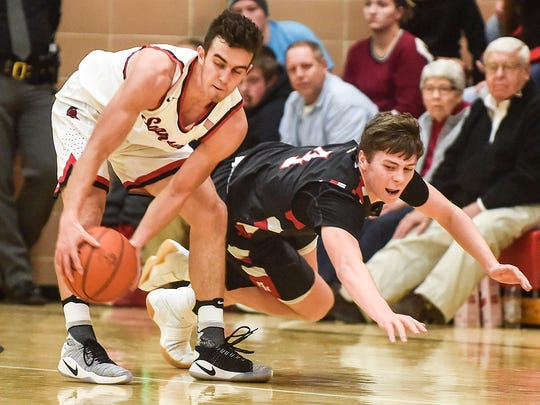 Pleasant's Hayden Craycraft (left) recovers a ball just before Marion Harding's Jason Ellis makes a dive for it during the Marion Harding versus Pleasant basketball game Friday night.