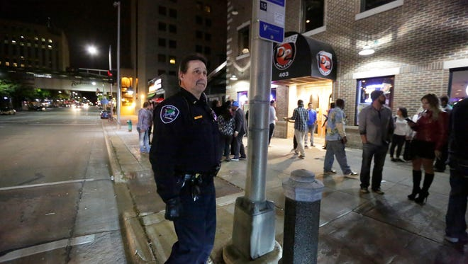 Lt. Jay Steinke of the Appleton Police Department keeps an eye on College Avenue in Appleton, Wis., Saturday night, October 3, 2015, into the early hours of Sunday morning. The walk brings Steinke into contact with the public, many who have developed an appreciation over the years for the way he deals with people.Ron Page/Post-Crescent Media