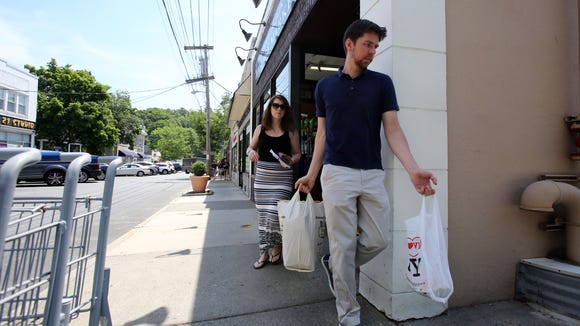Montrose residents Thomas Winkelmann and Noelle Hanks, who work in the village, leave Chappaqua Village Market with groceries June 2.