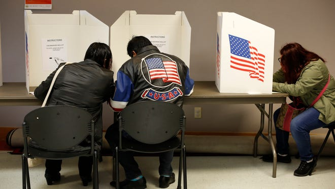 Voters fill out their ballots Tuesday, Nov. 8, 2016, at the Forest Avenue Public Library polling place on election day in Des Moines.
