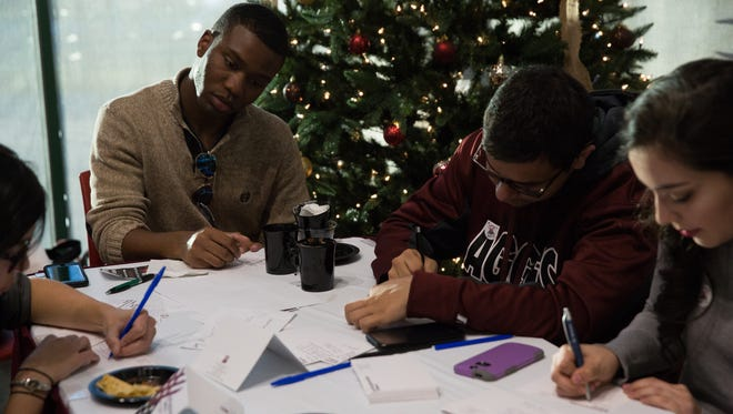 New Mexico State University students Haley Stewart, from left, DeLorean Forbes, Marcus Sanchez and Linda Cisneros write thank you cards Tuesday, Nov. 29, 2016, to those who donated to the university during Giving Tuesday. The soft total for the day was $1,913,534. The final total will be release Wednesday, once the phone lines close as midnight at Corbett Center in the Aggie Lounge.