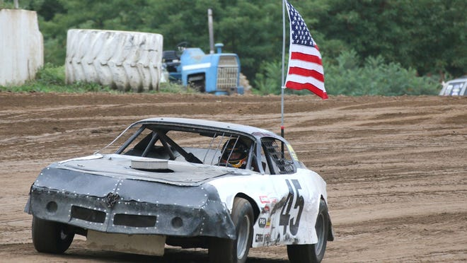 John C. Reeve's oldest grandson, Lewis carried the American flag around the track at Butler Motor Speedway Saturday night during the John C. Reeve Memorial. Lewis carried the flag while driving Reeve's last race car. Reeve passed away Sept. 2, 2017.