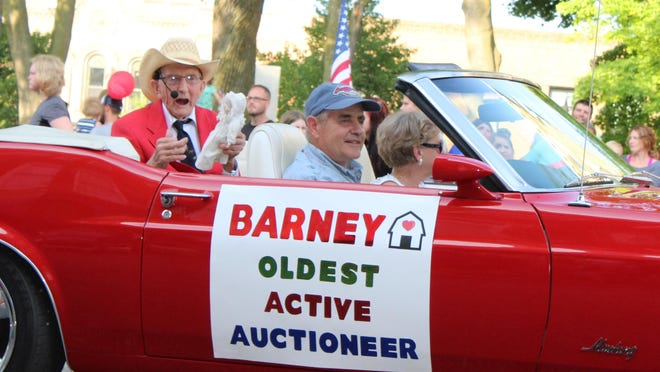 Barney Barnhart holds a doll being auctioned in the Great American Parade in Hillsdale several years ago.