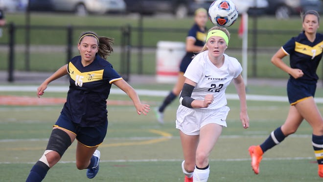 Plymouth freshman Elle McCaslin (22) and Saline's Bella Petrock (15) track down the bouncing ball Friday at Dearborn.