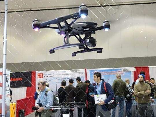 Drones fly in a cage on display at the International
