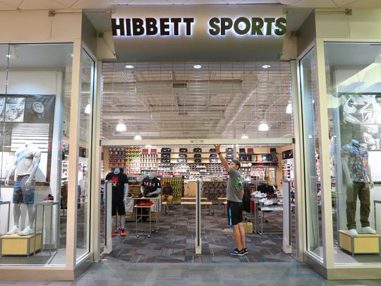 Hibbett team manager Andy Lewis opens the gate to the store at the Anderson Mall on Thursday to let an employee in. The store opens Saturday morning.