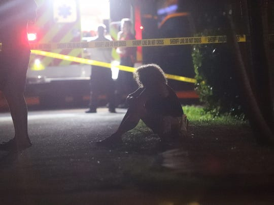 A woman grieves at an officer involved shooting on 400 block of Lazy Way.