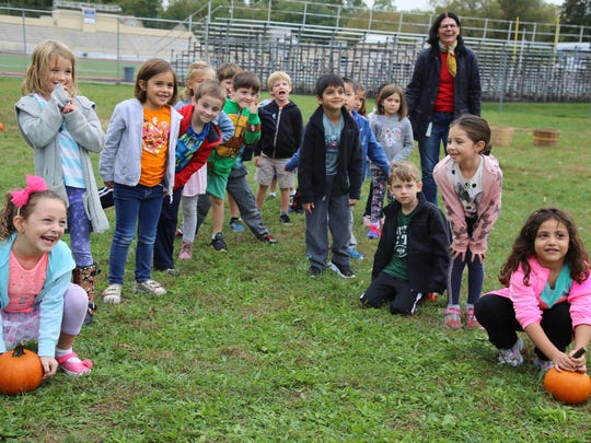 The Lincoln School's kindergarteners from Linda Steele's class participate in a pumpkin-themed relay race.