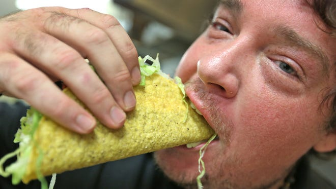 Chance Honeycutt takes a big bite of a tasty Paul Bunyan taco at the Roscoe's Tacos,  6845 S. Bluff Road, Indianapolis.