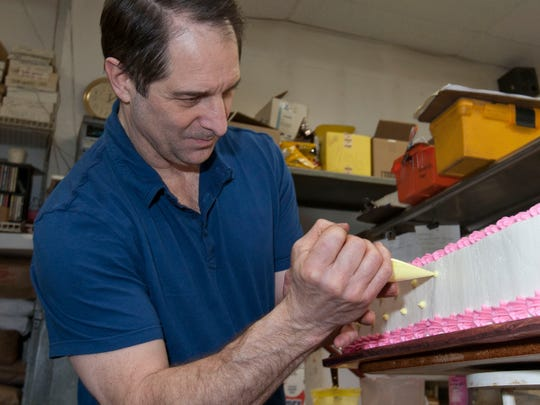 Tom Caruso, owner of Ye Olde Pie Shoppe in Little Silver, decorates a birthday cake.