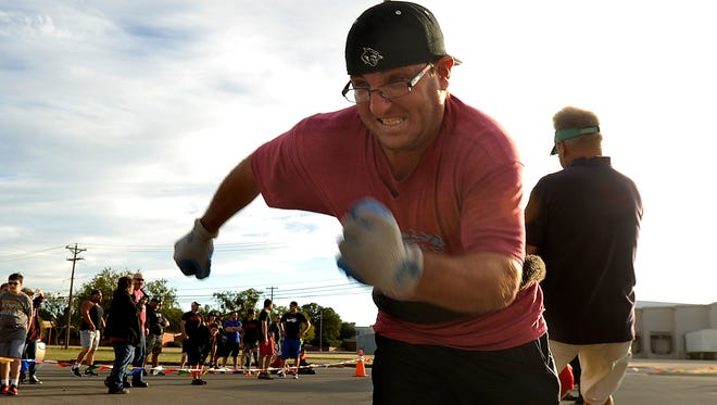Tagen Reeves with the Mustangs team gives everything he's got helping his team drag an Abilene fire truck across the parking lot of the Texas Roadhouse during the Abilene Fire Truck Pull Challenge to benefit the Special Olympics on Saturday, Oct. 29, 2016.