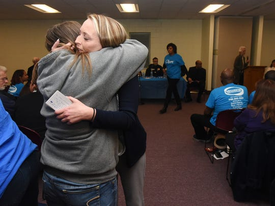 Nicole Withrow, right, hugs Velvet Boggs after Withrow spoke about her personal recovery story at a town hall meeting Monday at the Chillicothe & Ross County Public Library in downtown Chillicothe.