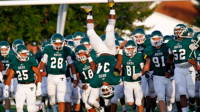 Trinity High School's Jailen Reed (34) does a flip as his team is lead out onto the field before their football game against Carmel High School at Trinity High School in Louisville, Kentucky.       August 29, 2014