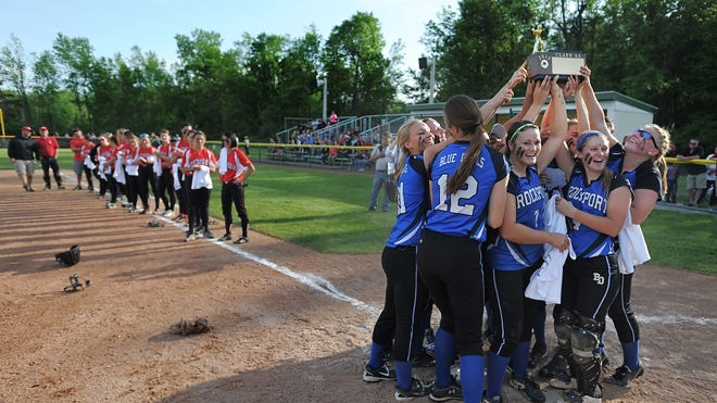 Brockport players lift the championship trophy as Penfield players look on following the Section V Class AA Softball Championship. Brockport beat Penfield 1-0 to win the Class AA title.
