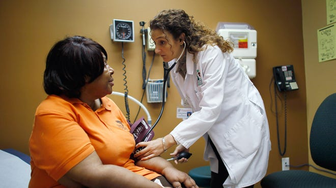 Brenda Major, left, who said she had a pre-existing condition that made it impossible to find insurance that would cover her until the Affordable Care Act, is examined by Dr. Fernanda Mercade during a routine checkup at the Jessie Trice Center for Community Health clinic last year in Miami. Some doctors say they don't even know if they are listed on insurance plans on the new ACA health exchanges, however.