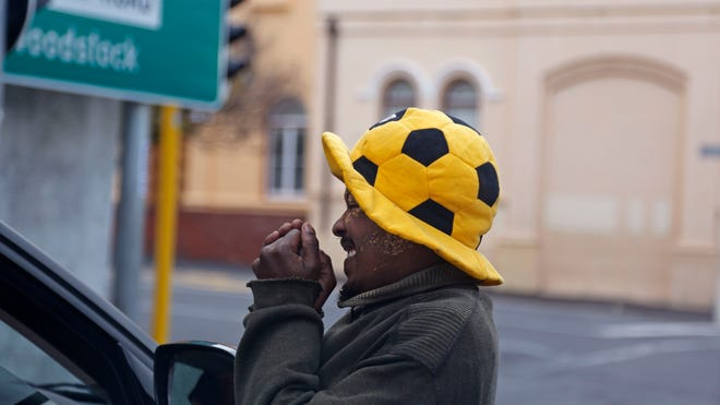 A homeless man wearing a soccer ball-shaped hat reacts after a person gave him money as he begs for a living in a city that hosted games during the 2010 World Cup in Cape Town, South Africa, ON June 14.