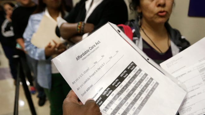 Ricky Spain, a financial counselor at Parkland Hospital, answers questions March 31, 2014, for people waiting to sign up for health insurance at the business office of Parkland Hospital in Dallas.